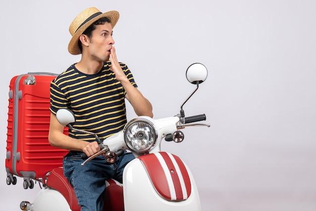 Vorderansicht des verwirrten jungen mannes mit strohhut auf moped, der hand zu seinem mund setzt