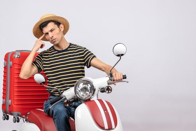 Vorderansicht des verwirrten jungen mannes mit strohhut auf moped, der rabattkarte hält
