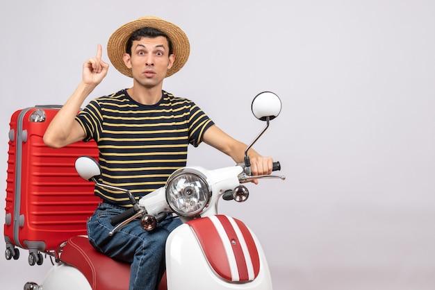 Vorderansicht des verwirrten jungen mannes mit strohhut auf moped, der zur decke zeigt