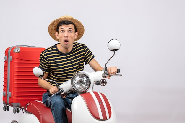 Vorderansicht des verwirrten jungen mannes mit strohhut auf moped