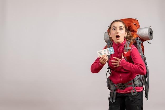 Vorderansicht des verwirrten jungen reisenden mit großem rucksack, der reiseticket auf grauer wand hält