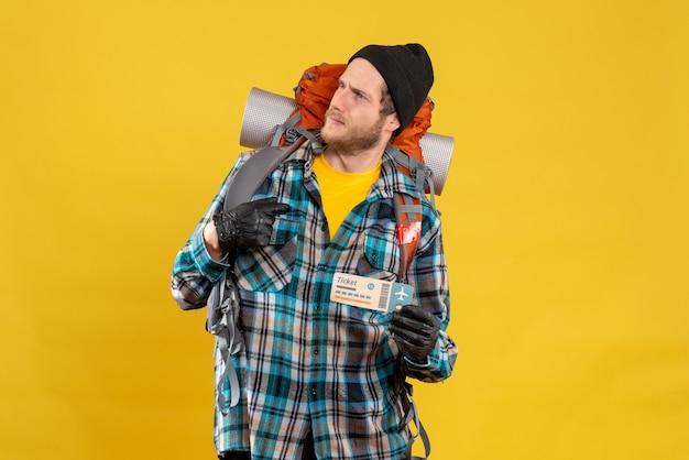 Vorderansicht des verwirrten jungen rucksacktouristen mit dem schwarzen hut, der das flugticket hält, das auf sich zeigt