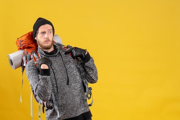 Vorderansicht des verwirrten jungen rucksacktouristen mit lederhandschuhen, die auf sich selbst zeigen