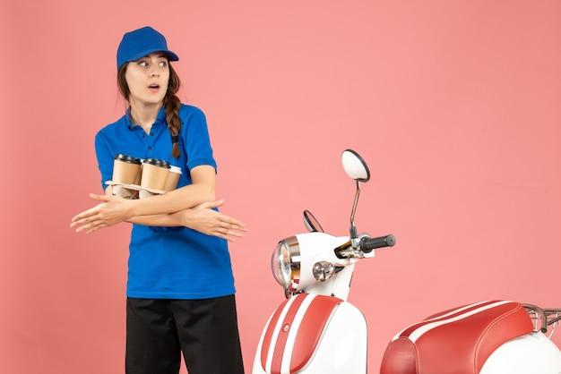 Vorderansicht des verwirrten kuriermädchens, das neben dem motorrad steht und kaffee auf pastellfarbenem pfirsichhintergrund hält