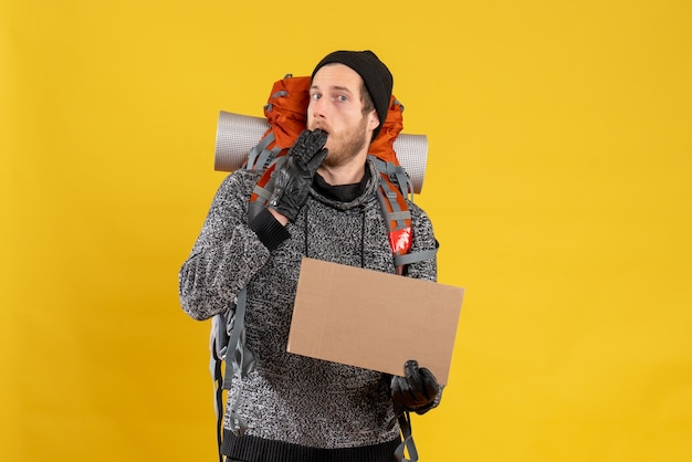 Vorderansicht des verwirrten männlichen anhängers mit lederhandschuhen und rucksack, der leeren karton hält