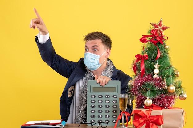 Vorderansicht des verwunderten geschäftsmannes, der rechner hält, der am tisch nahe weihnachtsbaum sitzt und auf gelb präsentiert