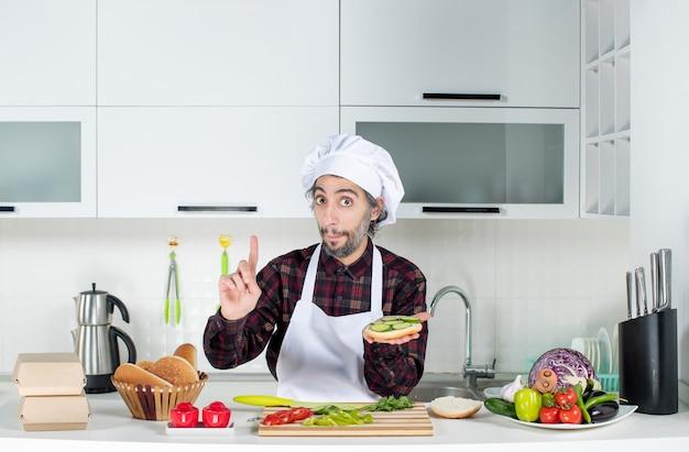 Vorderansicht des verwunderten männlichen kochs, der burger hinter dem küchentisch macht