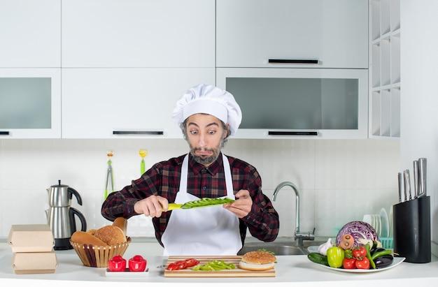 Vorderansicht des verwunderten männlichen kochs, der in der küche ein messer zum schneiden von gemüse hält