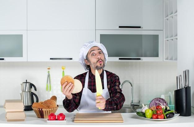 Vorderansicht des verwunderten männlichen kochs, der messer und brot in der küche hält