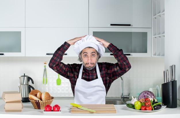 Vorderansicht des verwunderten mannes, der seinen kochhut auf dem tisch in der küche hält