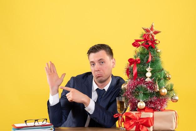 Vorderansicht des verwunderten mannfingers, der seine hand zeigt, die am tisch nahe dem weihnachtsbaum und den geschenken auf gelb sitzt