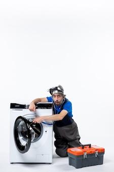 Vorderansicht des verwunderten mechanikers, der die tasche für die waschmaschinenwerkzeuge an der weißen wand öffnet