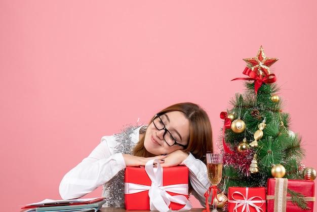 Vorderansicht des weiblichen arbeitnehmers, der geschenk auf rosa hält