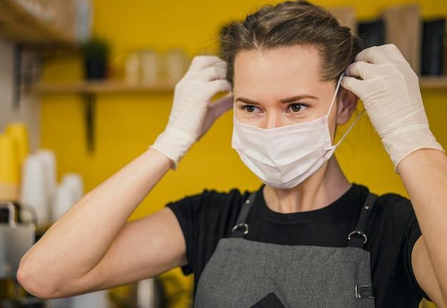 Vorderansicht des weiblichen barista, der medizinische maske aufsetzt