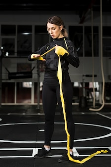 Vorderansicht des weiblichen boxers ihre hand in vorbereitung auf praxis einwickelnd