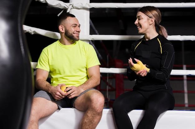 Vorderansicht des weiblichen boxers plaudernd mit trainer nahe bei ring