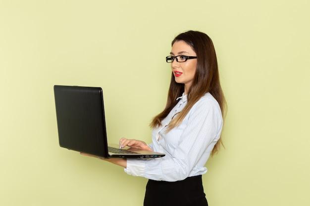 Vorderansicht des weiblichen büroangestellten im weißen hemd und im schwarzen rock, der laptop auf der hellgrünen wand hält