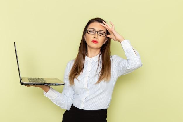 Vorderansicht des weiblichen büroangestellten im weißen hemd und im schwarzen rock, der laptop auf grüner wand hält