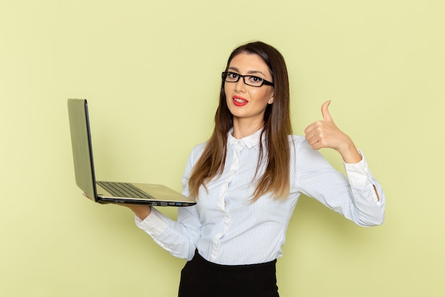 Vorderansicht des weiblichen büroangestellten im weißen hemd und im schwarzen rock, der unter verwendung des laptops an der grünen wand hält