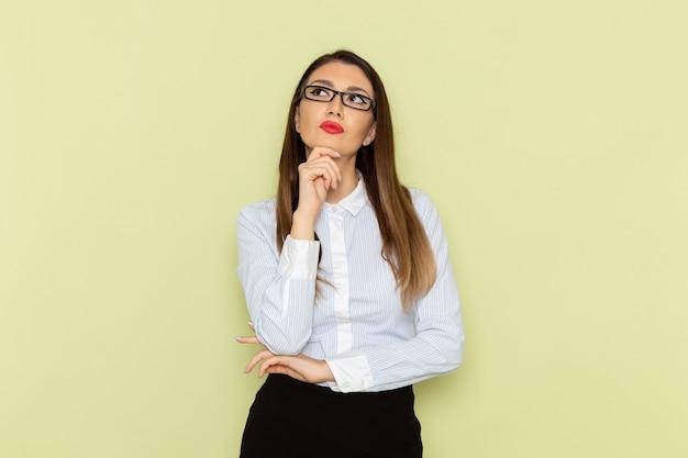 Vorderansicht des weiblichen büroangestellten im weißen hemd und im schwarzen rock, die auf grüner wand denken