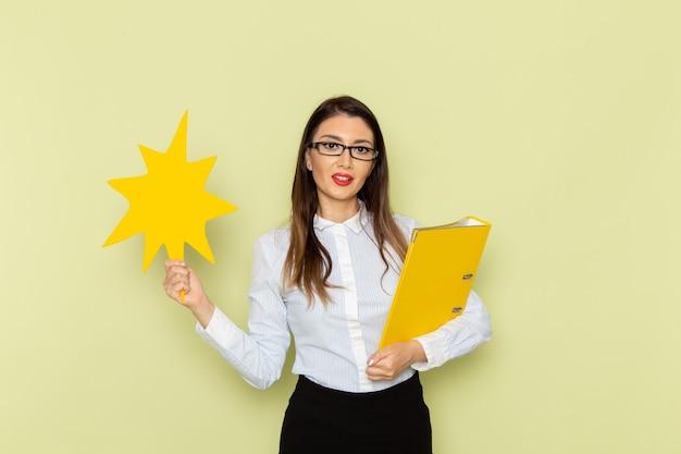 Vorderansicht des weiblichen büroangestellten im weißen hemd und im schwarzen rock, die ein großes gelbes zeichen und eine datei auf grüner wand halten
