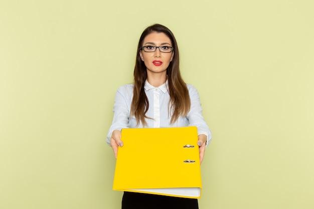 Vorderansicht des weiblichen büroangestellten im weißen hemd und im schwarzen rock, die gelbe datei an der grünen wand halten