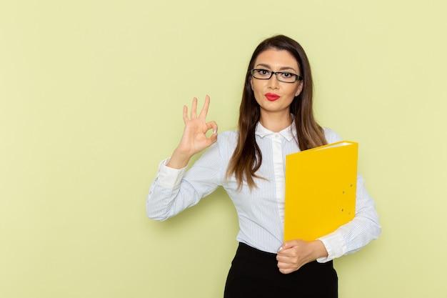 Vorderansicht des weiblichen büroangestellten im weißen hemd und im schwarzen rock, die gelbe datei halten und auf grüner wand aufwerfen