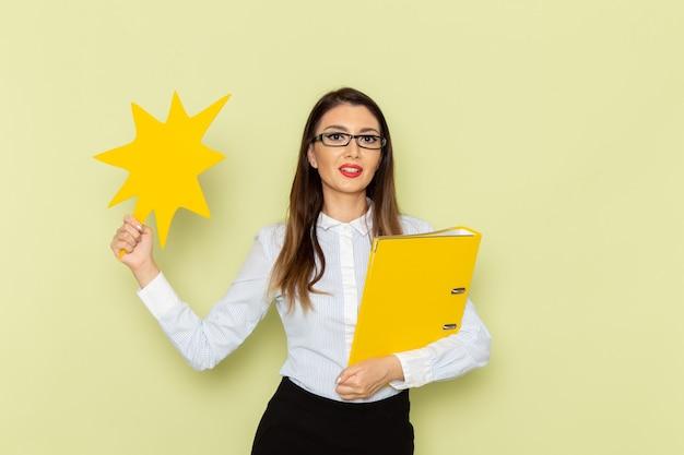 Vorderansicht des weiblichen büroangestellten im weißen hemd und im schwarzen rock, die gelbe datei und zeichen auf grüner wand halten