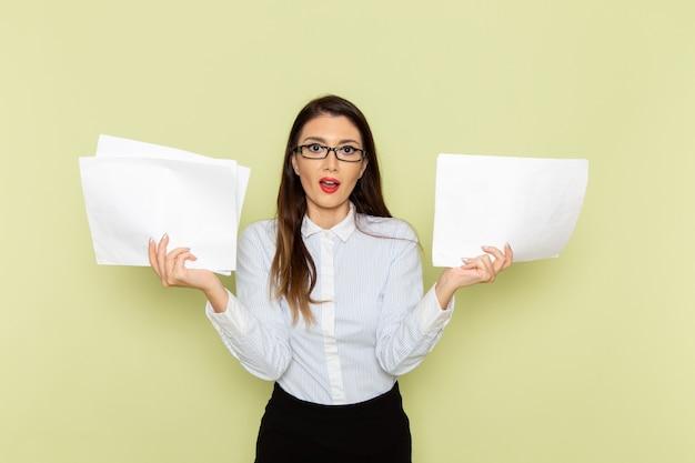 Vorderansicht des weiblichen büroangestellten im weißen hemd und im schwarzen rock, die papiere auf hellgrüner wand halten