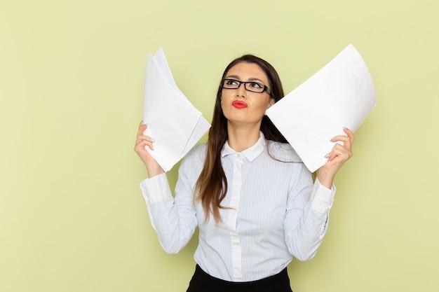 Vorderansicht des weiblichen büroangestellten im weißen hemd und im schwarzen rock, die papierkram an der grünen wand halten