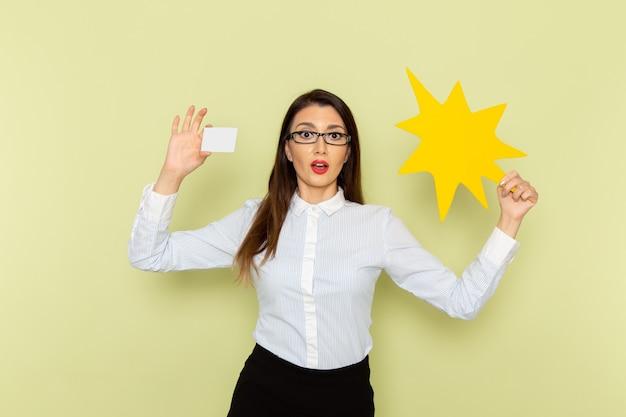 Vorderansicht des weiblichen büroangestellten im weißen hemd und im schwarzen rock, die weiße karte und gelbes zeichen auf grüner wand halten