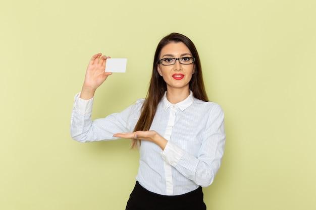 Vorderansicht des weiblichen büroangestellten im weißen hemd und im schwarzen rock, die weiße plastikkarte auf hellgrüner wand halten