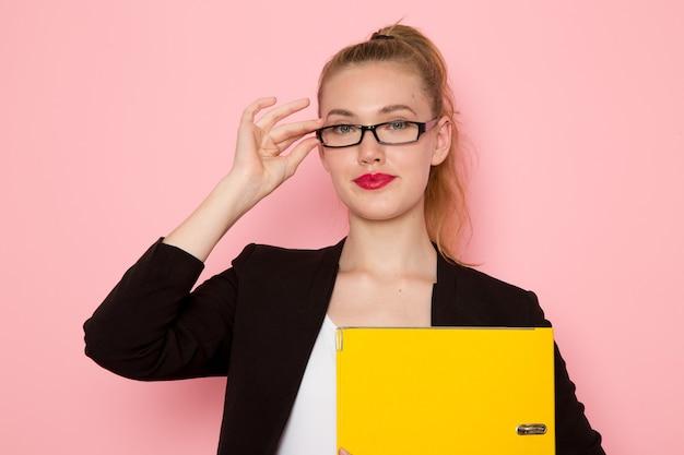 Vorderansicht des weiblichen büroangestellten in der schwarzen strengen jacke, die gelbe datei auf dem hellrosa schreibtischarbeitsjob-büroangestellter beschäftigt hält