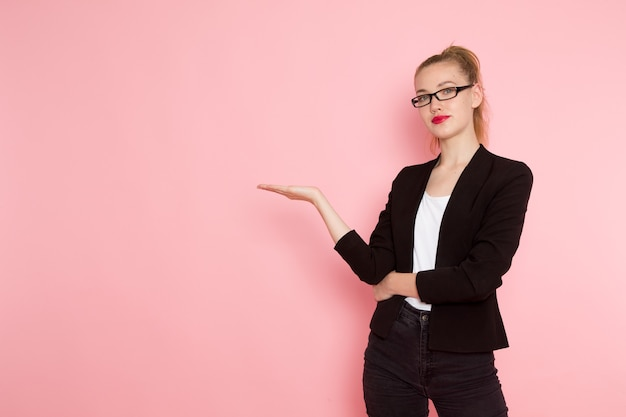 Vorderansicht des weiblichen büroangestellten in der schwarzen strengen jacke, die gerade auf der rosa wand aufwirft