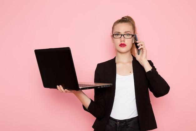 Vorderansicht des weiblichen büroangestellten in der schwarzen strengen strengen jacke, die laptop hält und unter verwendung auf hellrosa wand spricht