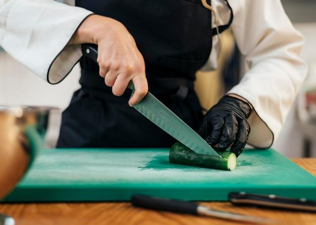 Vorderansicht des weiblichen kochs, der gurke schneidet
