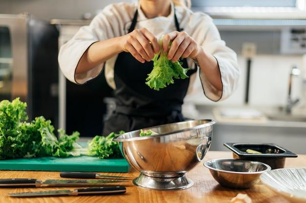 Vorderansicht des weiblichen kochs, der salat in der küche zerreißt