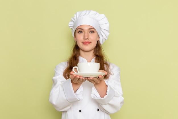 Vorderansicht des weiblichen kochs im weißen kochanzug, der kaffee auf grüner wand hält
