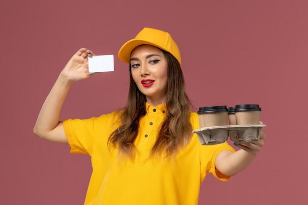 Vorderansicht des weiblichen kuriers in der gelben uniform und in der kappe, die braune kaffeetassen und karte auf der rosa wand halten
