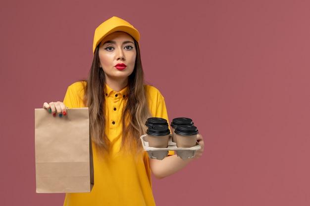 Vorderansicht des weiblichen kuriers in der gelben uniform und in der kappe, die braune kaffeetassen und nahrungsmittelpaket auf der rosa wand halten