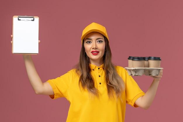 Vorderansicht des weiblichen kuriers in der gelben uniform und in der kappe, die braune kaffeetassen und notizblock an der rosa wand halten