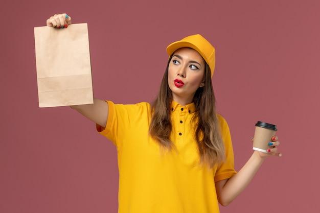 Vorderansicht des weiblichen kuriers in der gelben uniform und in der kappe, die die kaffeetasse und die lebensmittelverpackung der lieferung auf rosa wand hält