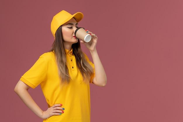 Vorderansicht des weiblichen kuriers in der gelben uniform und in der kappe, die kaffee auf der rosa wand trinkt