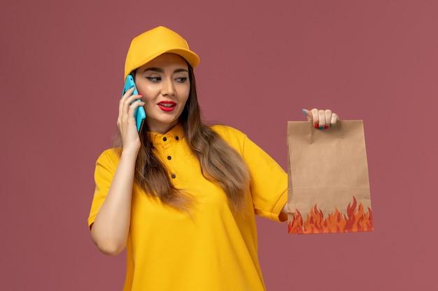 Vorderansicht des weiblichen kuriers in der gelben uniform und in der kappe, die lebensmittelpaket hält und am telefon auf rosa wand spricht
