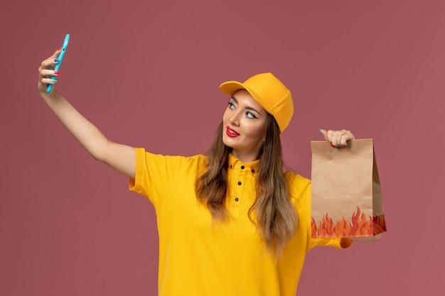 Vorderansicht des weiblichen kuriers in der gelben uniform und in der kappe, die nahrungsmittelpaket hält und ein selfie auf der rosa wand nimmt