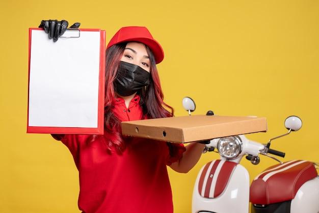 Vorderansicht des weiblichen kuriers in der maske mit der nahrungsmittelbox und der aktennotiz an der gelben wand