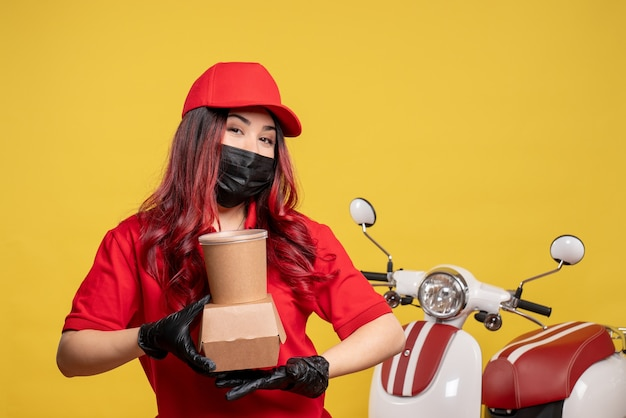 Vorderansicht des weiblichen kuriers in der maske mit liefernahrung auf gelber wand