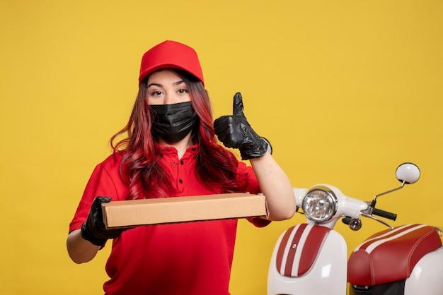 Vorderansicht des weiblichen kuriers in der maske mit liefernahrungsmittelbox auf gelber wand