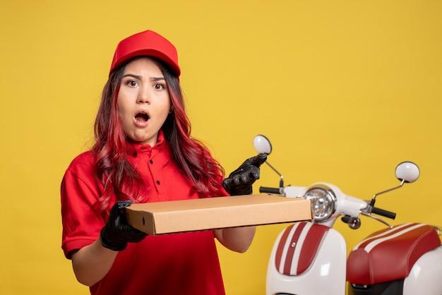 Vorderansicht des weiblichen kuriers mit nahrungsmittelbox auf gelber wand