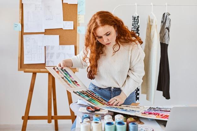 Vorderansicht des weiblichen modedesigners, der mit farbpalette im atelier arbeitet